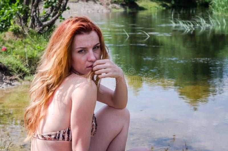 Muchacha hermosa joven en un bañador que se sienta en el banco del día soleado del verano del río fotos de archivo