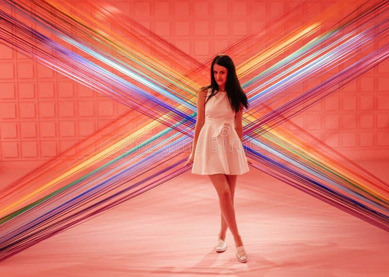 Muchacha hermosa joven en un fondo rosado de hilos coloridos fotografía de archivo
