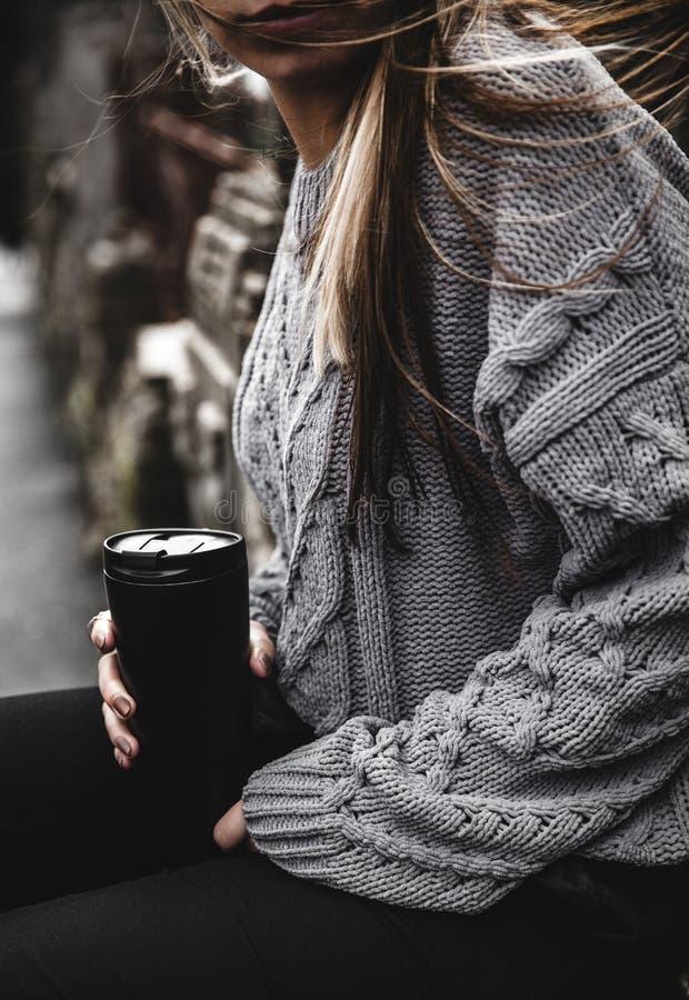 Muchacha hermosa joven en un suéter hecho punto caliente y las botas que presentan en la calle, en el porttrait de la calle, para foto de archivo libre de regalías