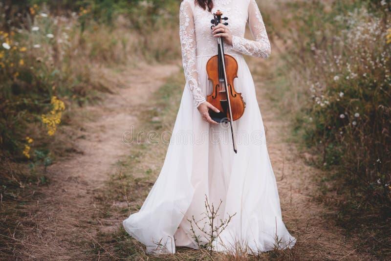 Muchacha hermosa joven en un vestido blanco debajo del árbol que sostiene un violín en manos imagen de archivo