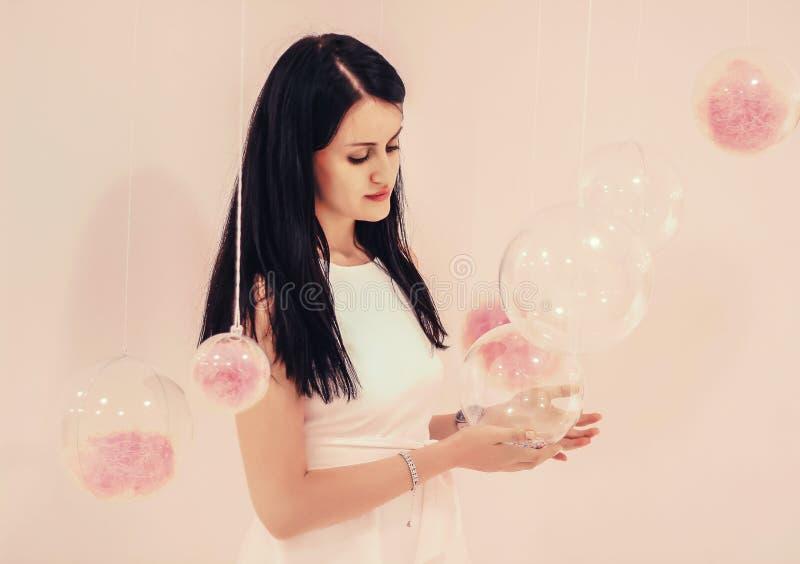 Muchacha hermosa joven en un vestido blanco en un fondo rosa claro de globos transparentes con un llenador rosado foto de archivo