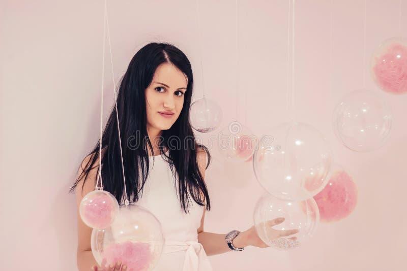 Muchacha hermosa joven en un vestido blanco en un fondo rosa claro de globos transparentes con un llenador rosado imágenes de archivo libres de regalías