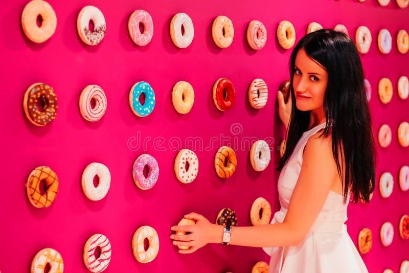 Muchacha hermosa joven en un vestido blanco en un fondo rosado de anillos de espuma multicolores imagenes de archivo