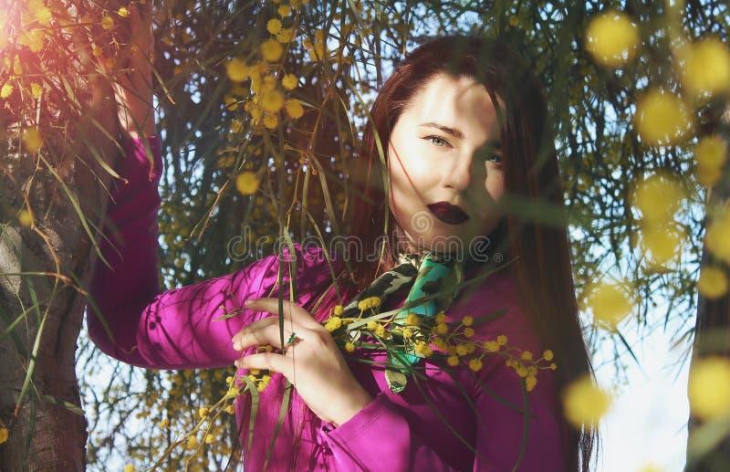Muchacha hermosa joven en un vestido rosado brillante con un ramo de YE imagen de archivo