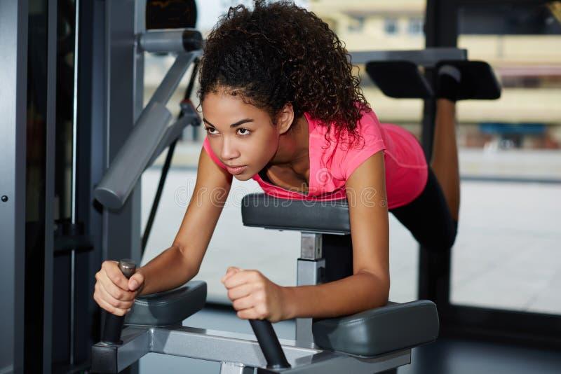 Muchacha hermosa joven en una camisa de deporte brillante que hace ejercicios en sus pies en pasillo de deportes foto de archivo