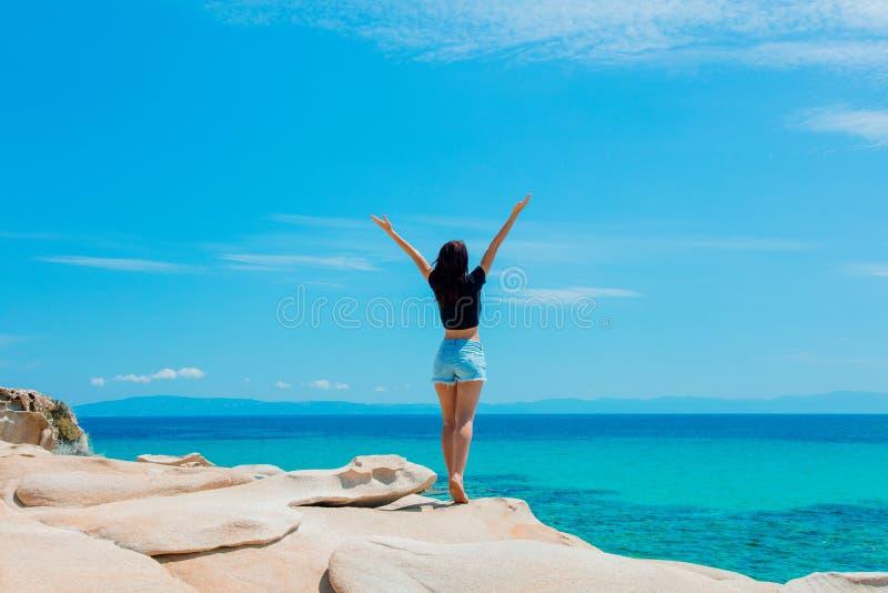 Muchacha hermosa joven en una roca cerca de una costa de mar fotos de archivo