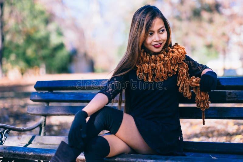Muchacha hermosa joven en vestido negro con la bufanda marrón que se sienta en el banco foto de archivo libre de regalías