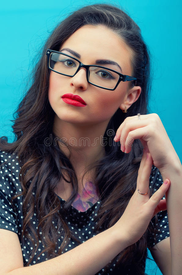 Muchacha hermosa joven en vidrios y con maquillaje fotos de archivo