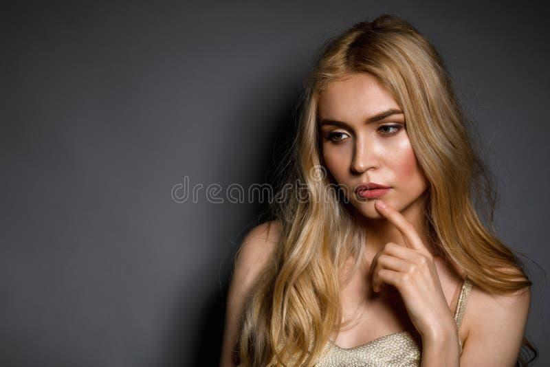 Muchacha hermosa joven pensativa en fondo gris con el espacio de la copia fotos de archivo libres de regalías