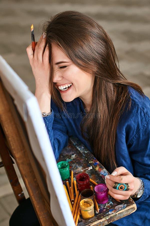Muchacha hermosa joven, pintor de sexo femenino del artista que sonríe, riendo y haciendo que un facepalm gesticula el pensamient imagen de archivo