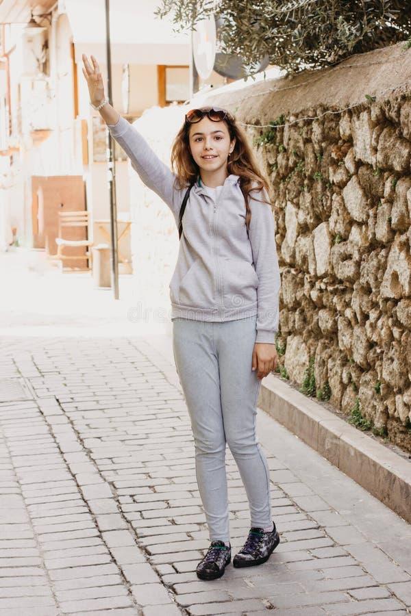 Muchacha hermosa joven que agita su mano alguien y que sonríe en la calle de la ciudad vieja imagen de archivo