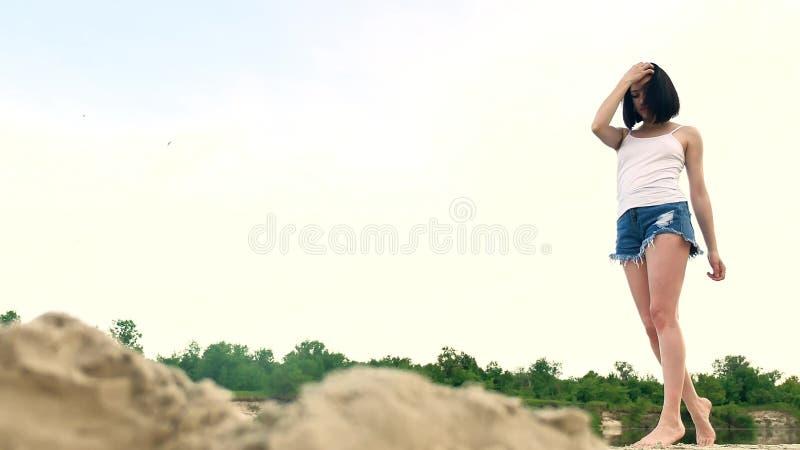 Muchacha hermosa joven que camina en la playa en la puesta del sol La mujer en la presentación blanca de la camiseta, del cabo y  imagen de archivo