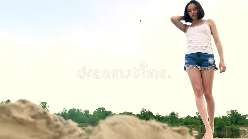Muchacha hermosa joven que camina en la playa en la puesta del sol La mujer en la presentación blanca de la camiseta, del cabo y  fotos de archivo