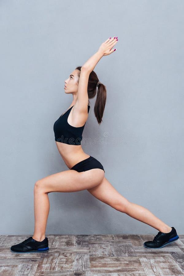 Muchacha hermosa joven que hace la yoga que presenta sobre un fondo gris imágenes de archivo libres de regalías