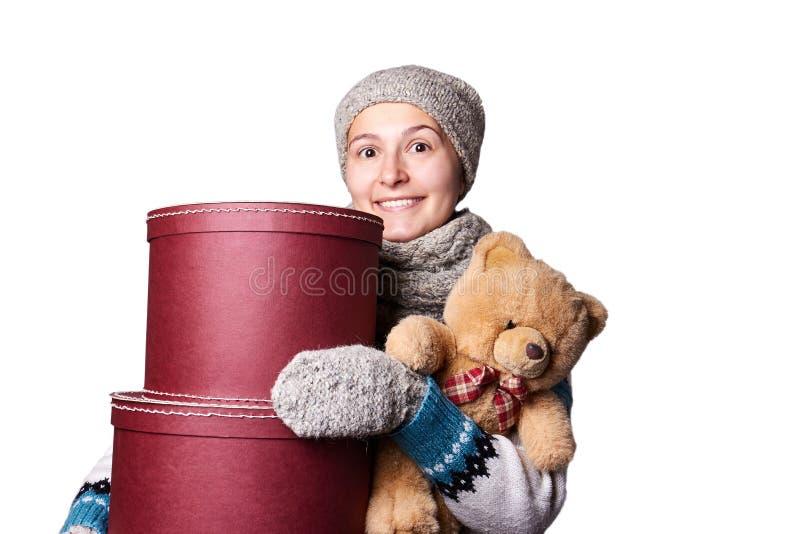 Muchacha hermosa joven que lleva a cabo el oso de peluche y la caja de fondo blanco fotos de archivo libres de regalías
