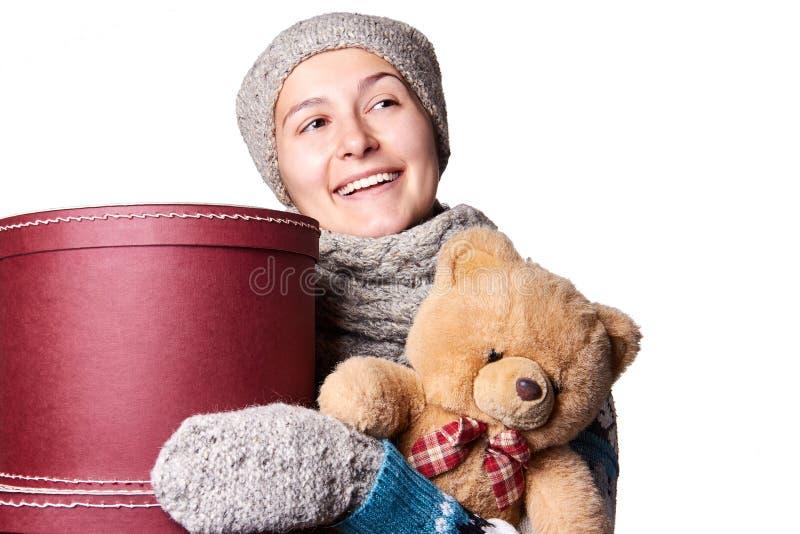 Muchacha hermosa joven que lleva a cabo el oso de peluche y la caja de fondo blanco imagenes de archivo