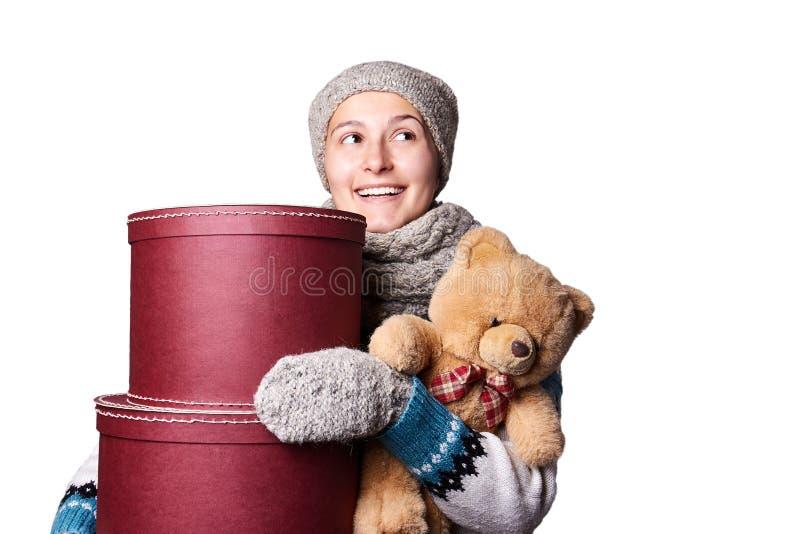 Muchacha hermosa joven que lleva a cabo el oso de peluche y la caja de fondo blanco imagen de archivo
