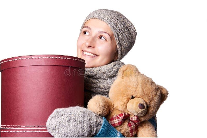 Muchacha hermosa joven que lleva a cabo el oso de peluche y la caja de fondo blanco fotografía de archivo