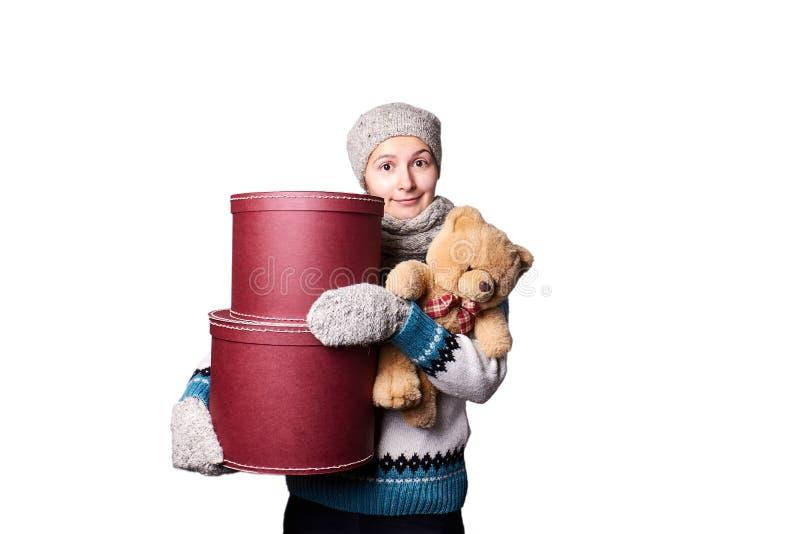 Muchacha hermosa joven que lleva a cabo el oso de peluche y la caja de fondo blanco fotos de archivo