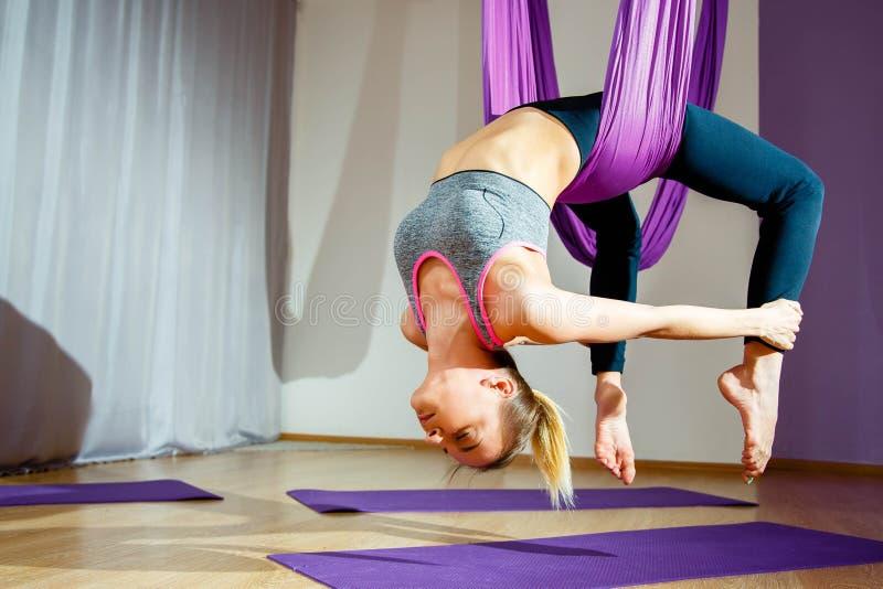 Muchacha hermosa joven que practica yoga aérea en gimnasio imagen de archivo libre de regalías