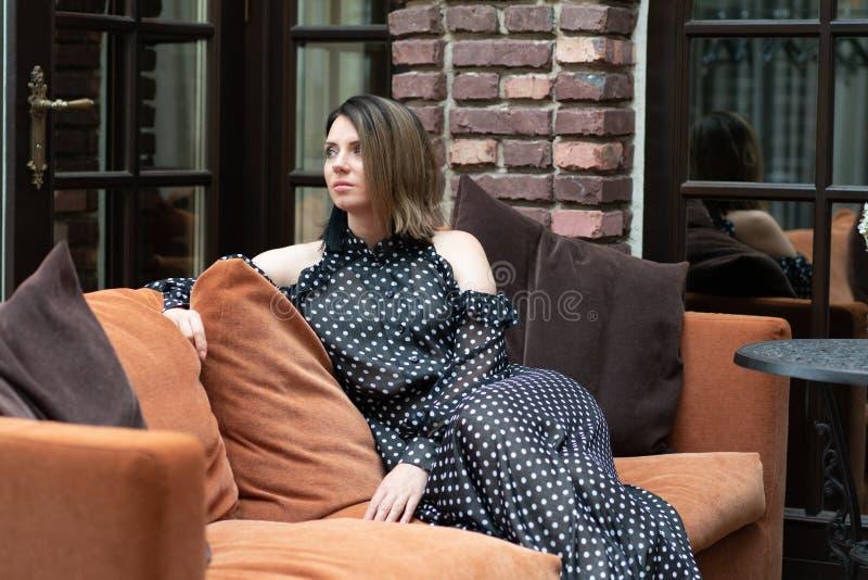Muchacha hermosa joven que presenta en un exterior que se sienta del sof? imágenes de archivo libres de regalías