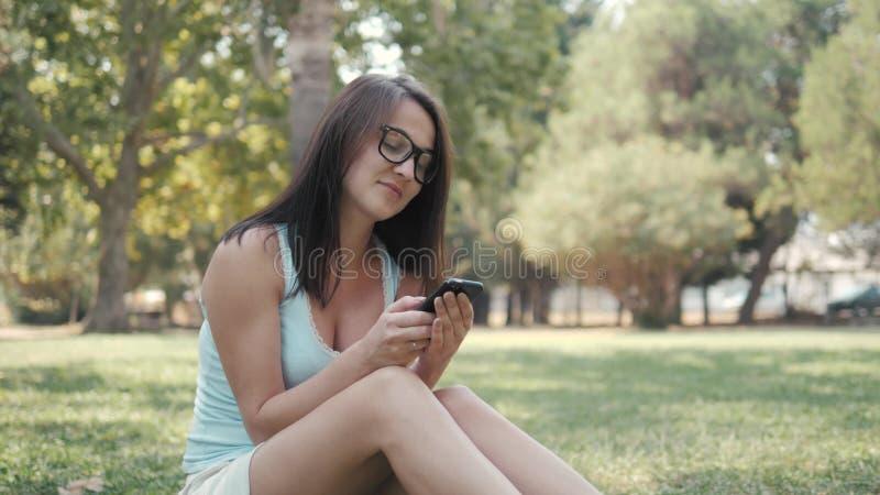 Muchacha hermosa joven que se sienta en césped en parque usando el teléfono, concepto en línea de las compras foto de archivo libre de regalías