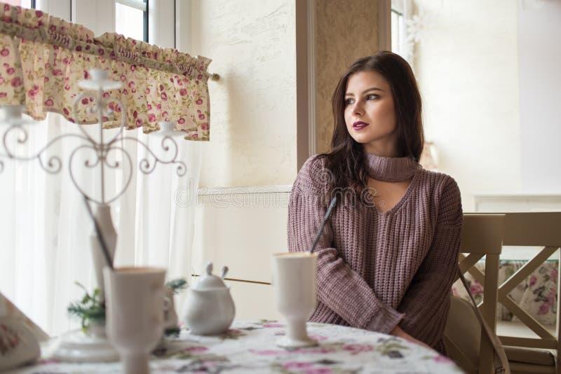 Muchacha hermosa joven que se sienta en café acogedor y que mira hacia fuera la ventana Latte fragante caliente en la tabla fotos de archivo libres de regalías