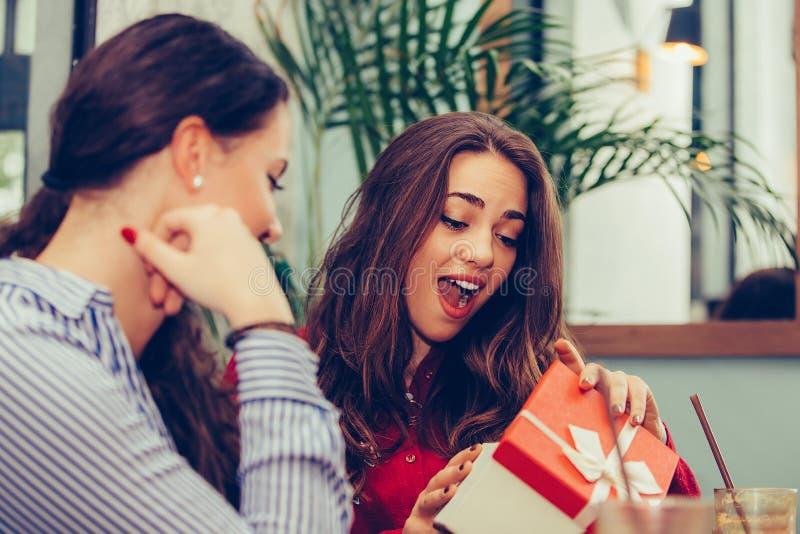 Muchacha hermosa joven que se sienta en caf? con su amigo y que recibe un regalo imagen de archivo libre de regalías