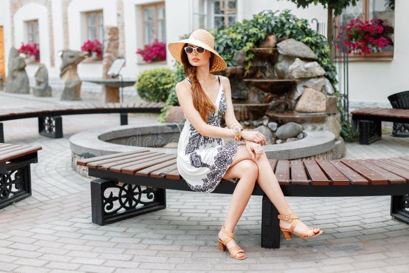 Muchacha hermosa joven que se sienta en un banco en un día de verano soleado foto de archivo libre de regalías