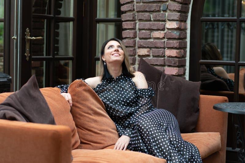 Muchacha hermosa joven que se sienta en un vestido en un sofá marrón f imágenes de archivo libres de regalías