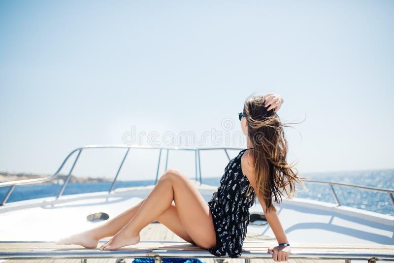 Muchacha hermosa joven que se sienta en un yate en el mar Relajación en el agua Mujer que descansa sobre el agua imagenes de archivo