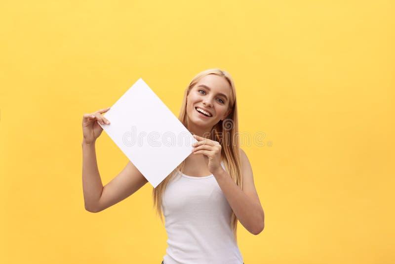 Muchacha hermosa joven que sonríe y que sostiene una hoja de papel en blanco, aislada en fondo amarillo en colores pastel fotos de archivo