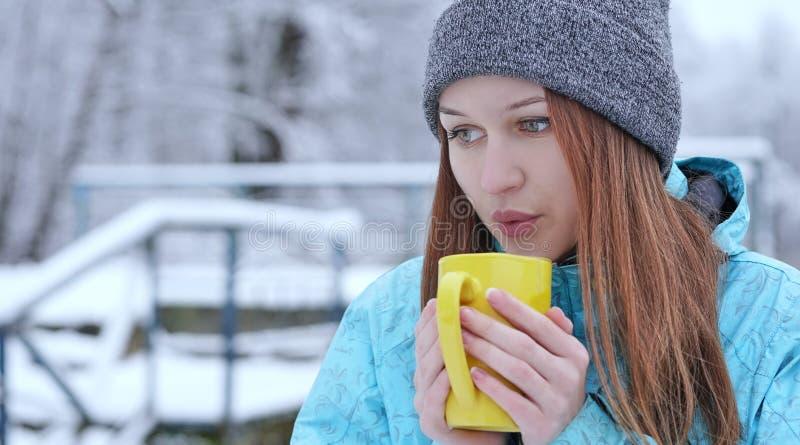 Muchacha hermosa joven que sopla en un té o un café caliente que se coloca en la orilla de un lago del invierno fotografía de archivo