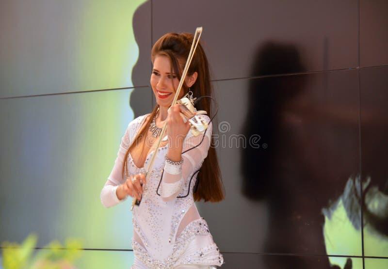 Muchacha hermosa joven que toca el violín en el centro de exposición fotos de archivo libres de regalías