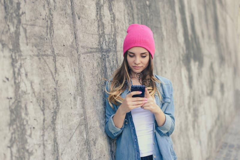 Muchacha hermosa linda en la ropa casual que coloca la pared cercana en la calle y que usa su smartphone para la comunicación en  imágenes de archivo libres de regalías