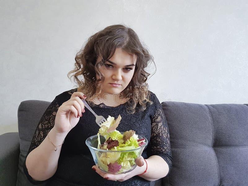Muchacha hermosa llena triste en el sofá con dieta de la ensalada fotografía de archivo