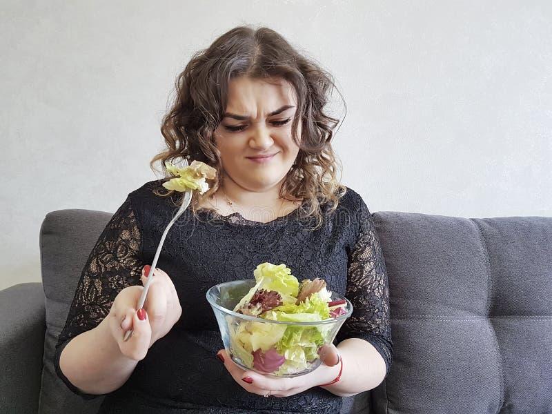 Muchacha hermosa llena triste en el sofá con la dieta del plato de la ensalada infeliz fotos de archivo