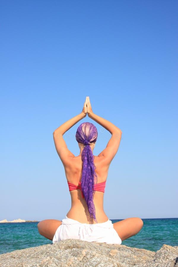 Muchacha hermosa meditating en la playa fotografía de archivo