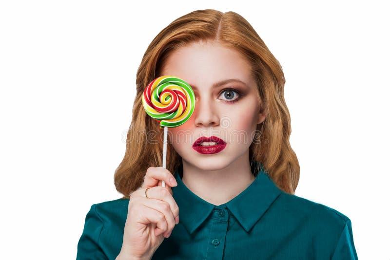 Muchacha hermosa pelirroja en una camisa verde con el caramelo redondo multicolor foto de archivo