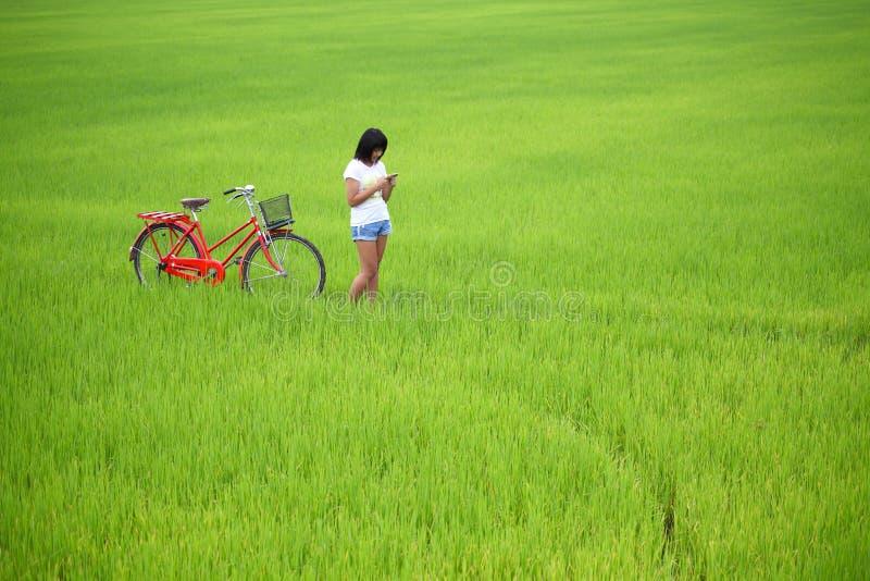 Muchacha hermosa plaing un teléfono con la bici fotos de archivo libres de regalías