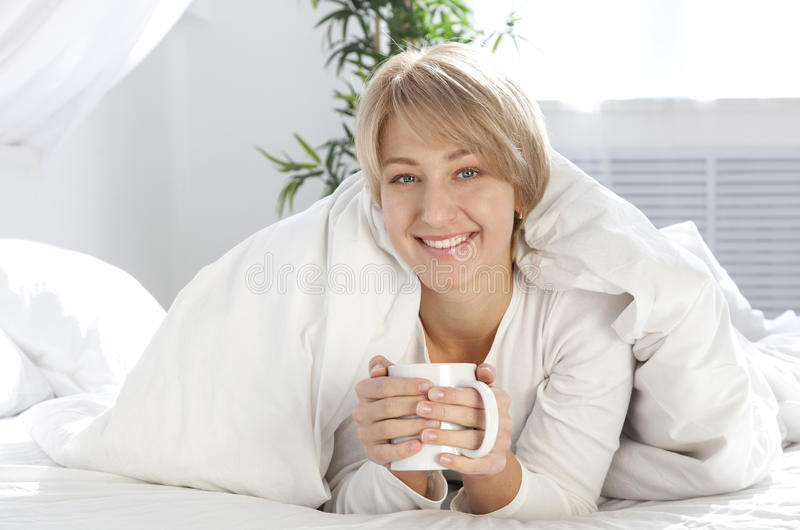 Muchacha hermosa por la mañana en cama con la taza fotos de archivo