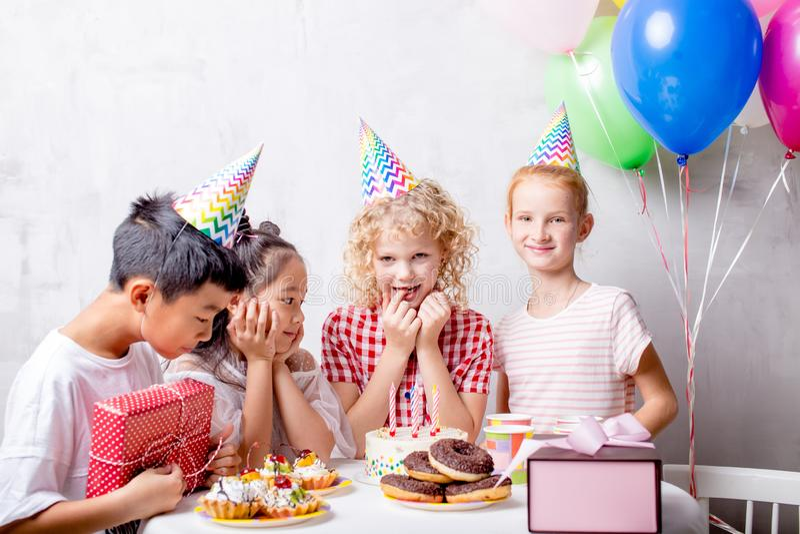 Muchacha hermosa positiva que hace un deseo en su fiesta de cumpleaños imágenes de archivo libres de regalías