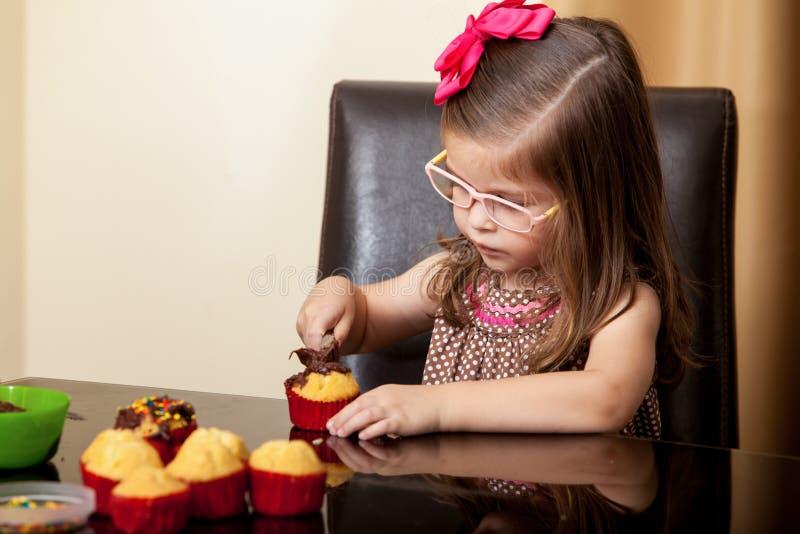 Muchacha hermosa que adorna las magdalenas foto de archivo libre de regalías
