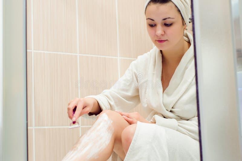 Muchacha hermosa que afeita sus piernas usando una maquinilla de afeitar mientras que toma la ducha en cuarto de baño foto de archivo