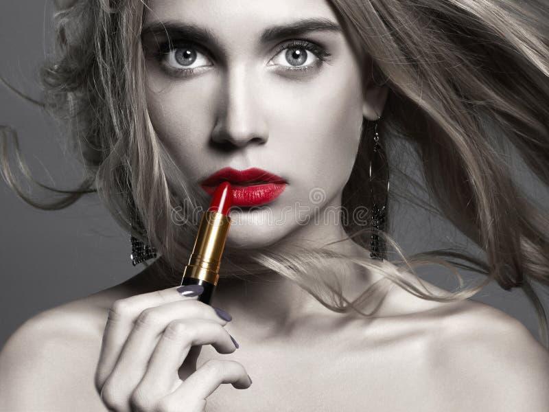 Muchacha hermosa que aplica el lápiz labial mujer joven que pone el lápiz labial rojo fotos de archivo
