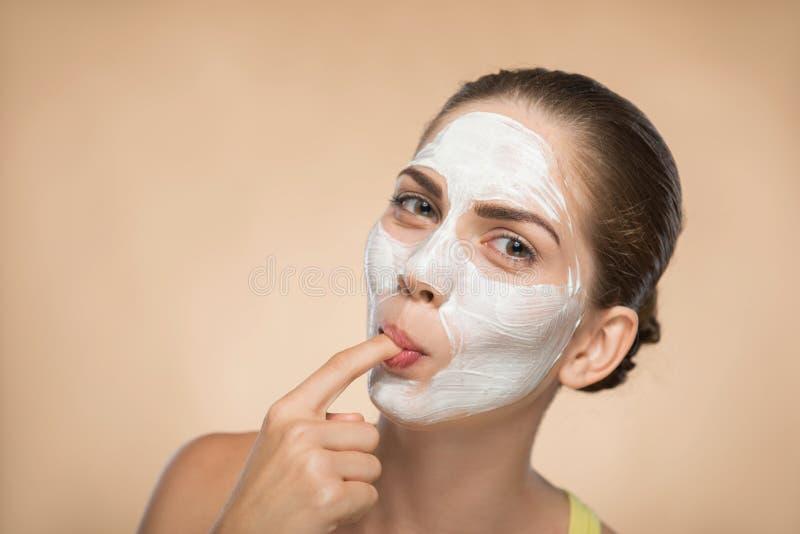 Muchacha hermosa que aplica la máscara poner crema facial y foto de archivo