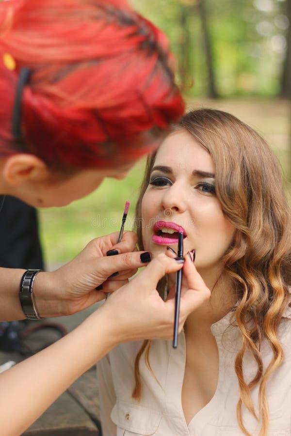Muchacha hermosa que aplica maquillaje imagen de archivo libre de regalías