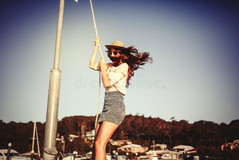 Muchacha hermosa que balancea con una cuerda en el puerto del ocio Concepto de la manera fotografía de archivo