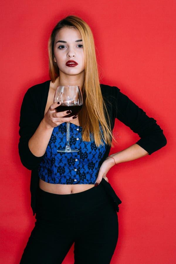 Muchacha hermosa que bebe el vino rojo imagenes de archivo