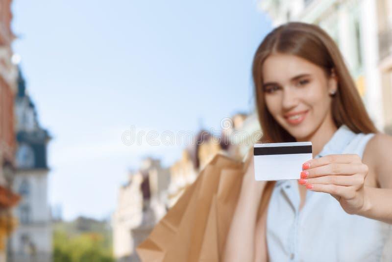 Muchacha hermosa que camina en una calle después de hacer compras imagen de archivo